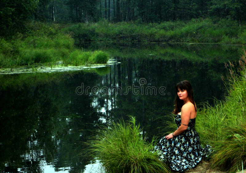 Charming woman on river coast royalty free stock images