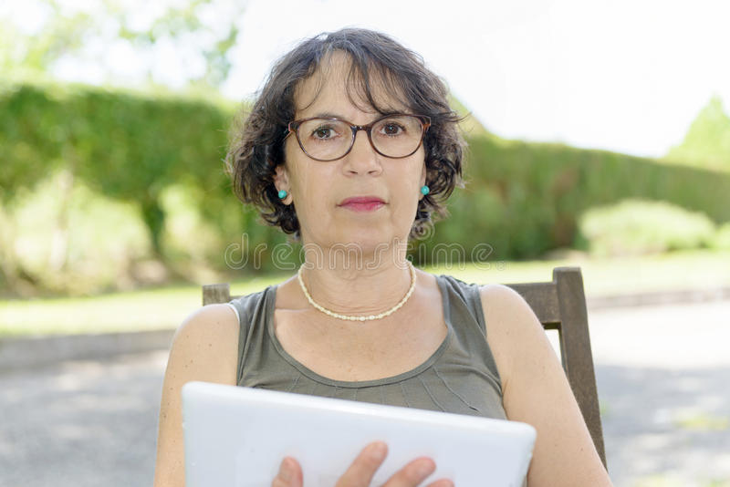 Charming woman with a tablet in her garden stock photos