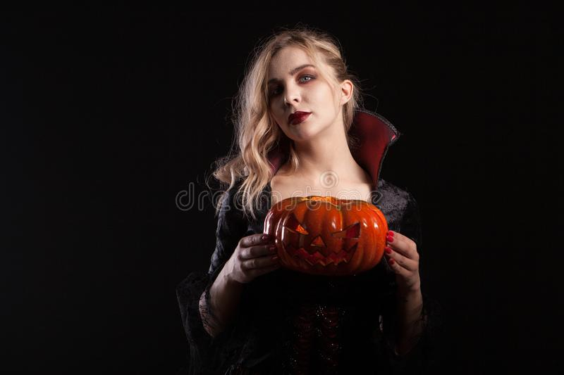 Charming woman in vampire costume holding halloween pumpkin on dark background. Stylish vampire woman royalty free stock photo