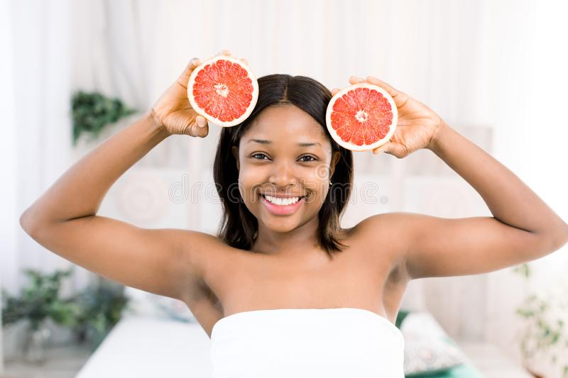 Charming young African girl holding slices of grapefruit in front of her face. Photo of smiling african american woman royalty free stock photos