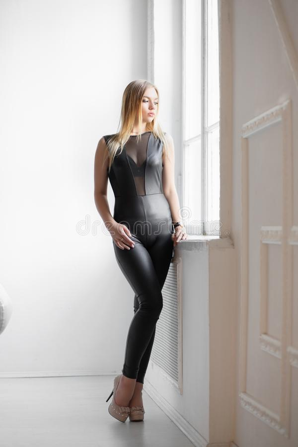Charming young blonde. Posing in the studio dressed in a black leather suit stock images