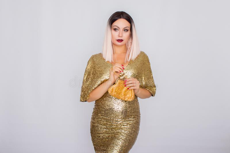 Charming young blonde haired woman wearing elegant gold evening dress and holding gold color clutch in her hands royalty free stock image