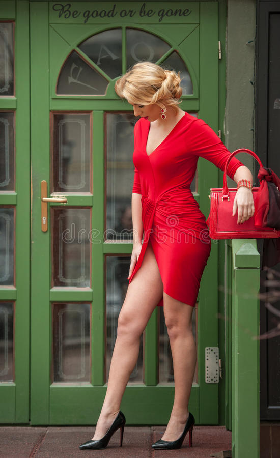 Free Charming Young Blonde In Red Dress Posing In Front Of A Green Painted Door Frame. Sensual Gorgeous Young Woman On High Heels Royalty Free Stock Photos - 67732028
