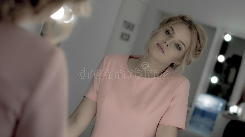 Charming young blonde with professional makeup and hairstyle look at mirror royalty free stock images
