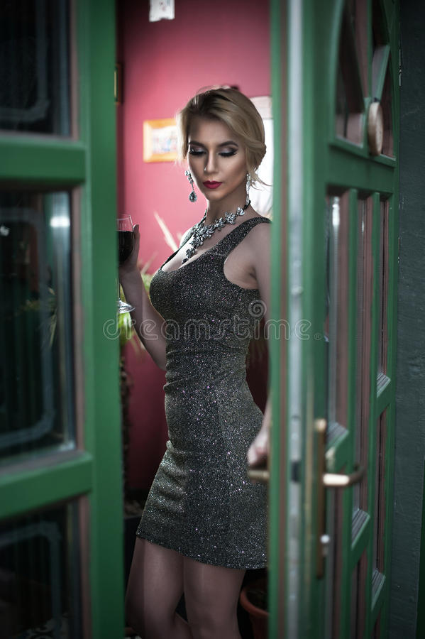 Charming young blonde with silver short tight fit dress posing in a green painted door frame. Sensual gorgeous young woman in gray stock photo