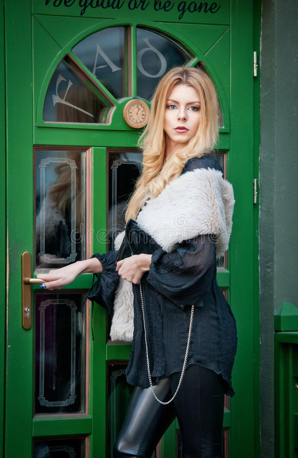 Charming young blonde woman with white fur posing in a green painted door frame. gorgeous young woman with long curly hair royalty free stock photo