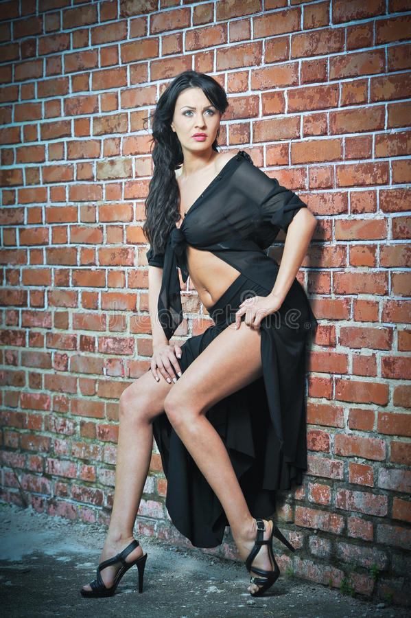 Charming young brunette woman in black and high heels staying near a red brick wall. Gorgeous young woman near old wall. Full length portrait of a provocative stock image