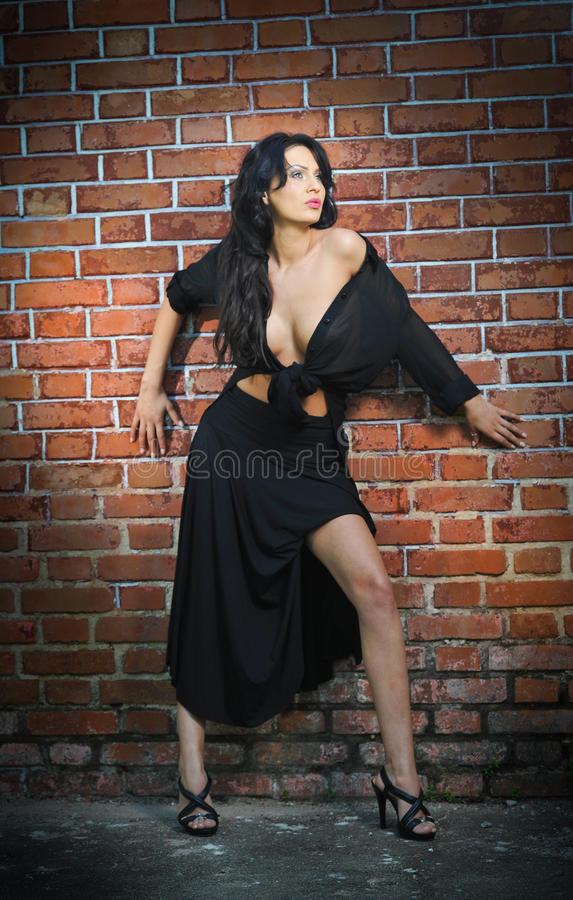 Charming young brunette woman in black and high heels staying near a red brick wall. Gorgeous young woman near old wall. Full length portrait of a provocative royalty free stock image