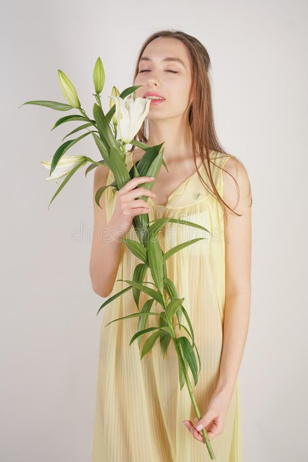 A charming young caucasian girl in a retro yellow pleated transparent nightie holds a lush Lily flower in her hands and stands on. A white background in the stock photo