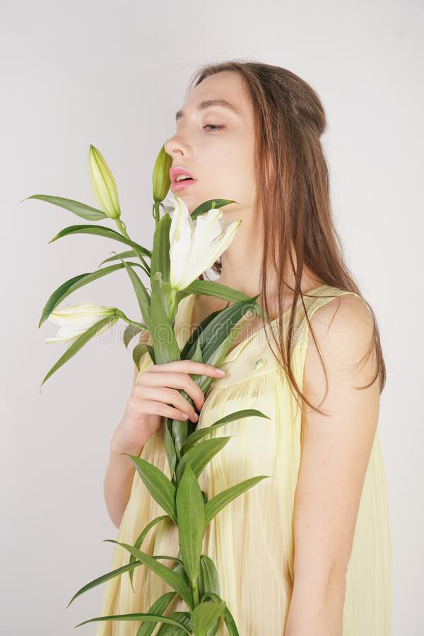 A charming young caucasian girl in a retro yellow pleated transparent nightie holds a lush Lily flower in her hands and stands on. A white background in the stock images