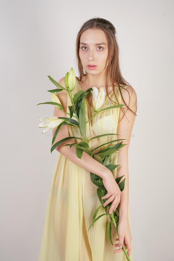 A charming young caucasian girl in a retro yellow pleated transparent nightie holds a lush Lily flower in her hands and stands on. A white background in the royalty free stock photos