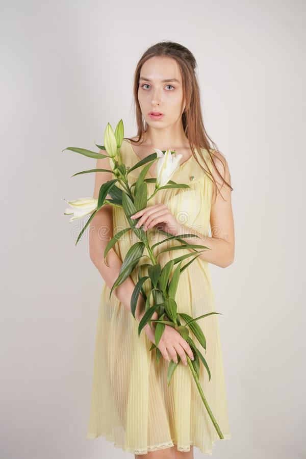 A charming young caucasian girl in a retro yellow pleated transparent nightie holds a lush Lily flower in her hands and stands on. A white background in the stock image