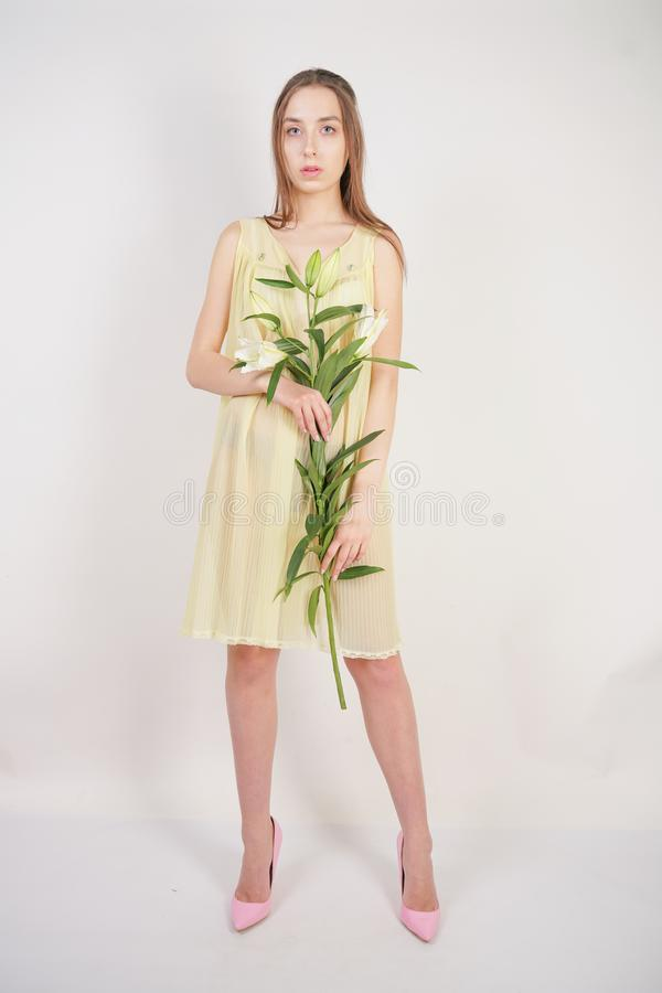 A charming young caucasian girl in a retro yellow pleated transparent nightie holds a lush Lily flower in her hands and stands on. A white background in the royalty free stock image