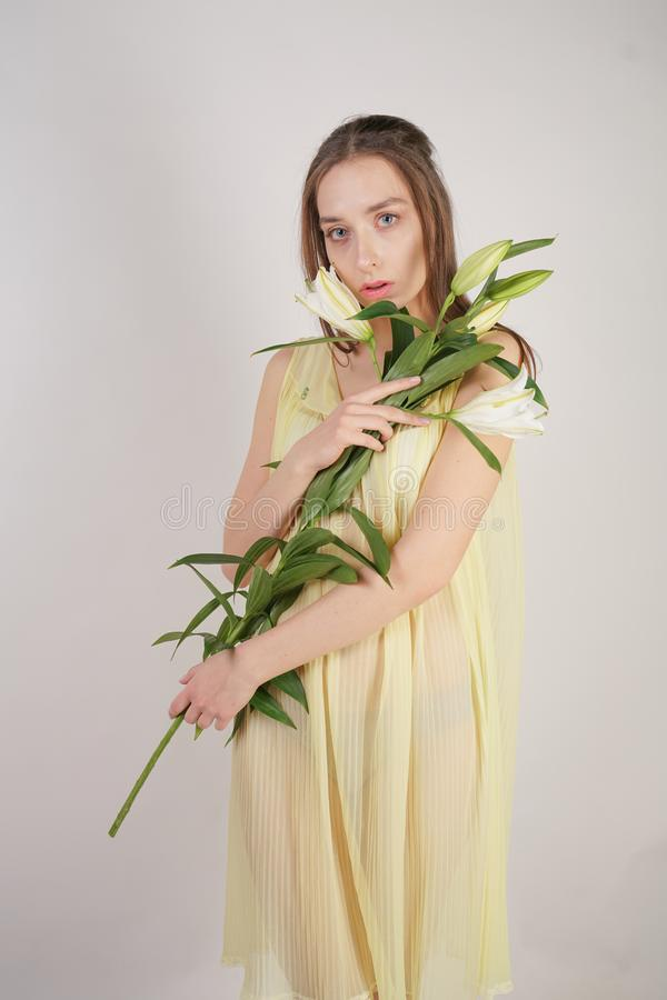 A charming young caucasian girl in a retro yellow pleated transparent nightie holds a lush Lily flower in her hands and stands on. A white background in the royalty free stock images