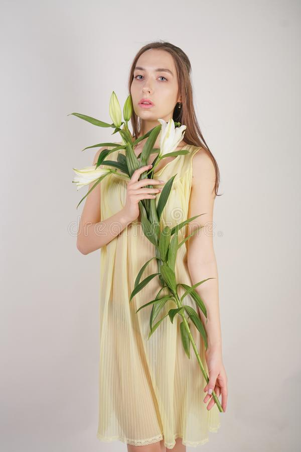A charming young caucasian girl in a retro yellow pleated transparent nightie holds a lush Lily flower in her hands and stands on. A white background in the stock photography