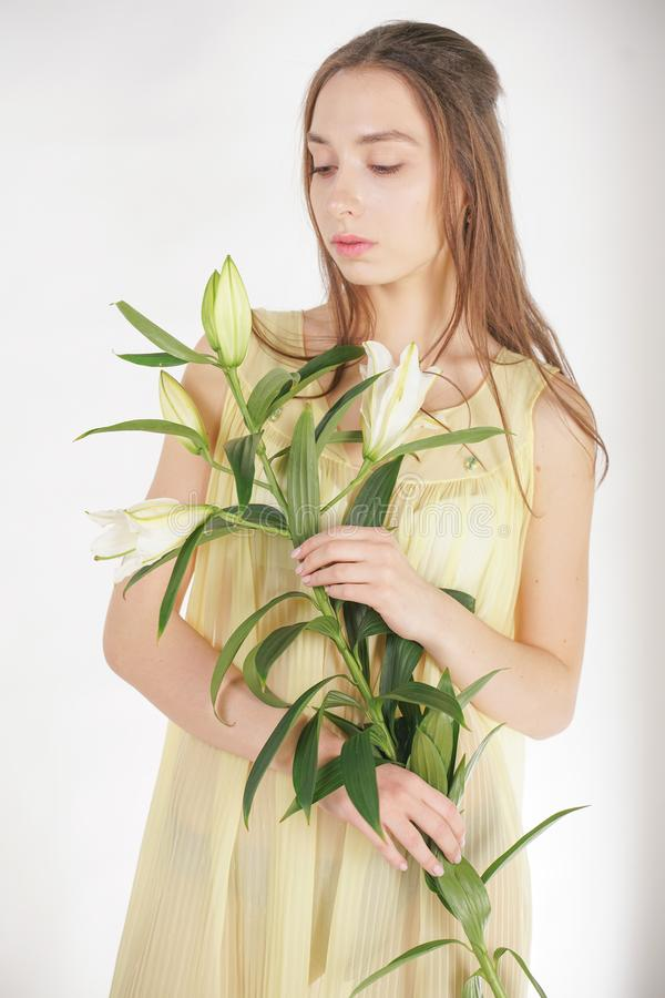 A charming young caucasian girl in a retro yellow pleated transparent nightie holds a lush Lily flower in her hands and stands on. A white background in the stock photos