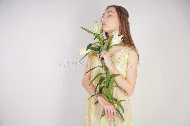 A charming young caucasian girl in a retro yellow pleated transparent nightie holds a lush Lily flower in her hands and stands on. A white background in the royalty free stock photography