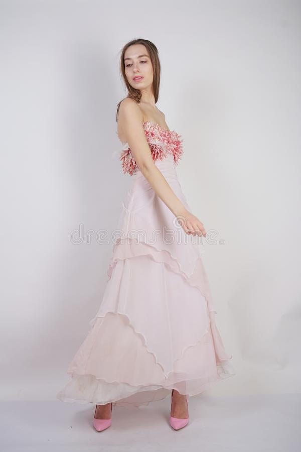 A charming young caucasian girl stands in a pink long prom dress with flower petals on her chest and poses on a white background i. N the Studio isolated stock photo
