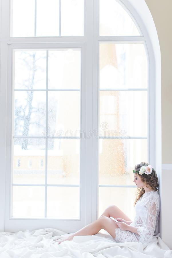 Charming young curly bride in white sitting royalty free stock photography