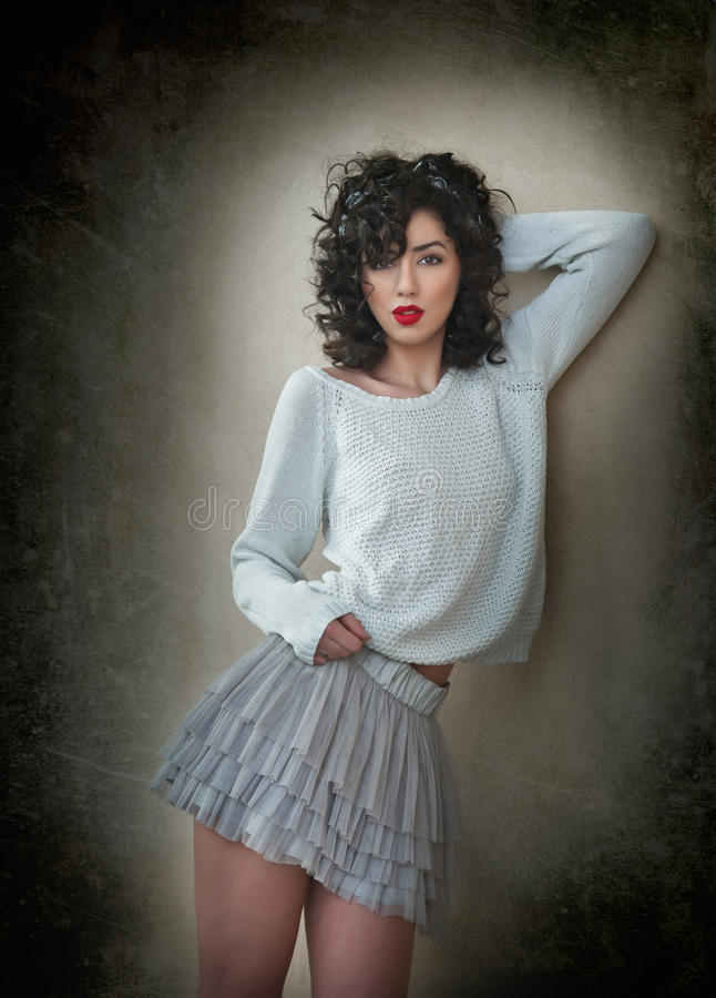 Charming young curly brunette woman in lace short skirt and white blouse leaning against wall. gorgeous young woman. With long legs near wall. Portrait of stock image