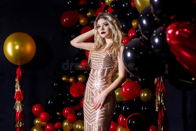 Beautiful girl in a dress on a studio in a ballons background royalty free stock images
