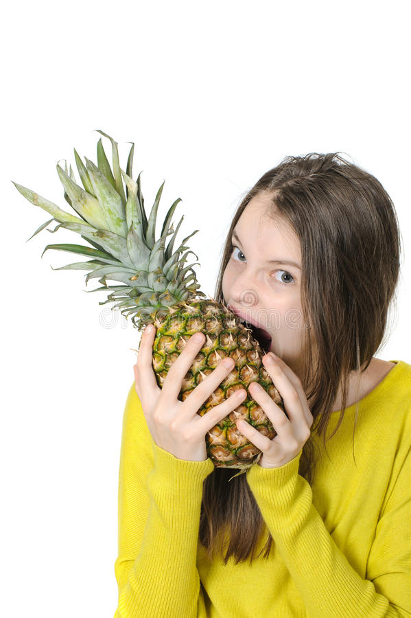 Charming young girl bites a large ripe pineapple. Charming young girl bites a large ripe pineapple on a clean white background stock photography