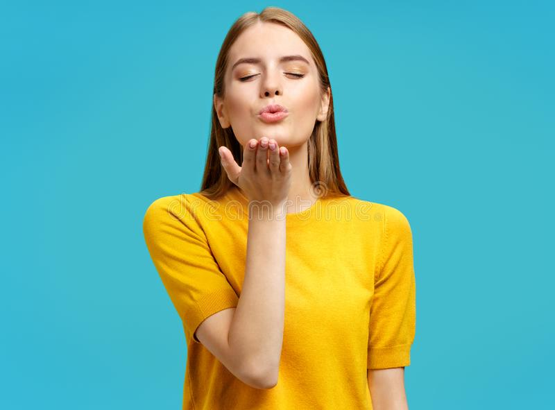 Charming young girl with closed eyes sends air sweet kiss. stock image