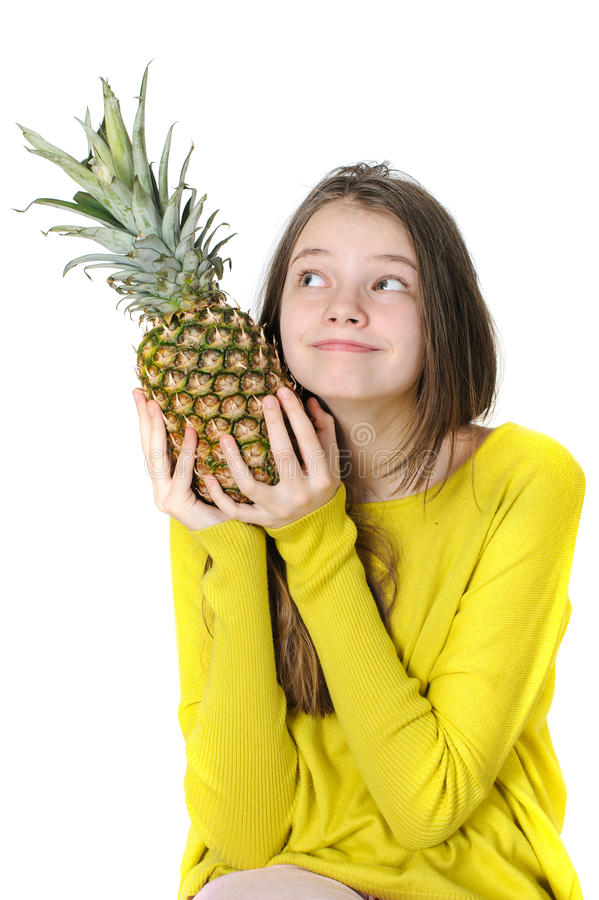 Charming young girl holding a large ripe pineapple and looking u royalty free stock photo