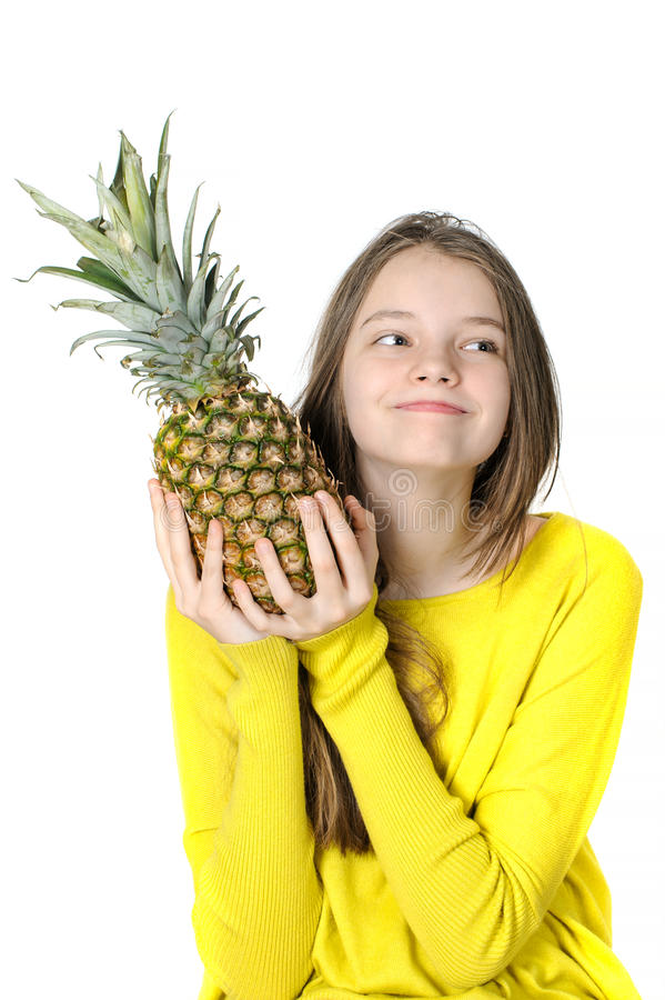 Charming young girl holds a large ripe pineapple in her hands an stock photos