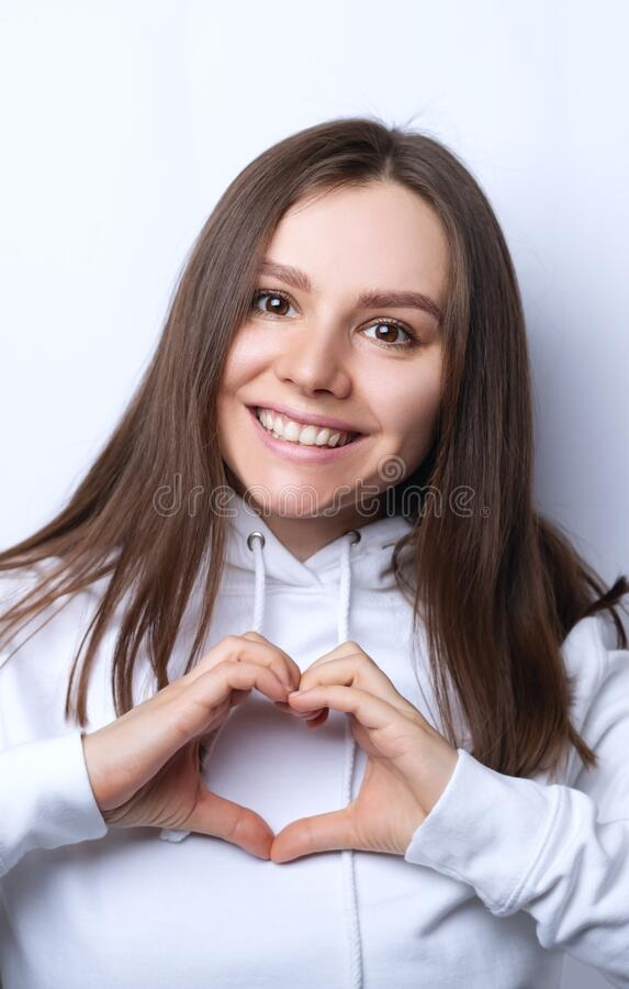 Free Charming Young Girlfriend Confesses In Love, Shows Heart Gesture, Smiles Broadly, Has Romantic Feelings Stock Image - 176291631