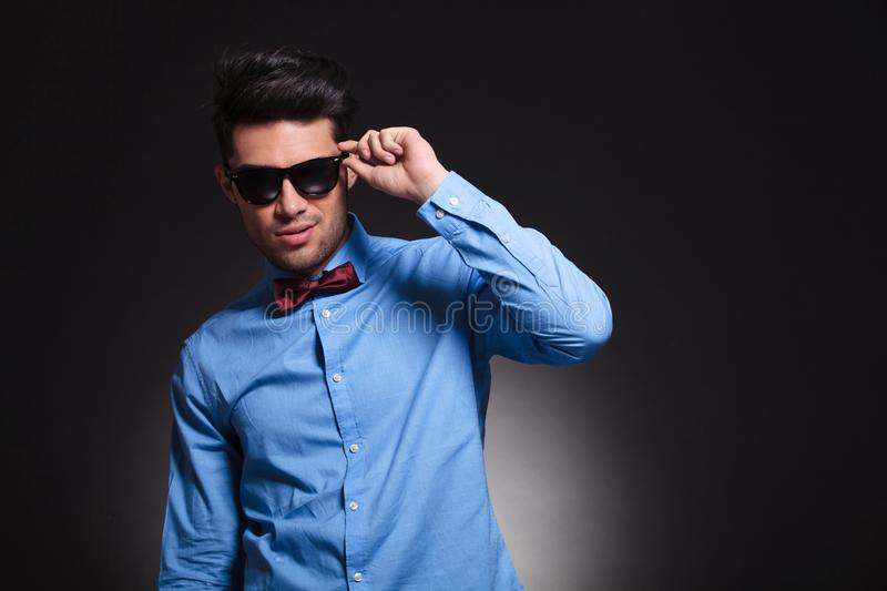 Charming young male standing and fixing his sunglasses stock images
