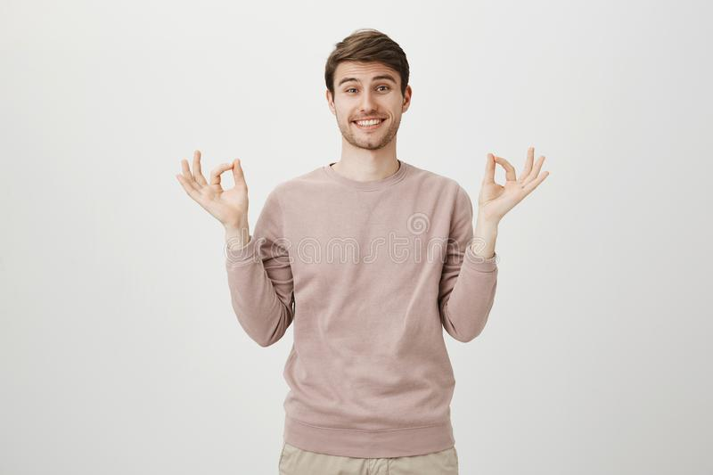 Charming young man with bright smile and bristle, wearing casual pullover and showing okay or zen gesture while standing. Over gray background. Coworker says royalty free stock photos