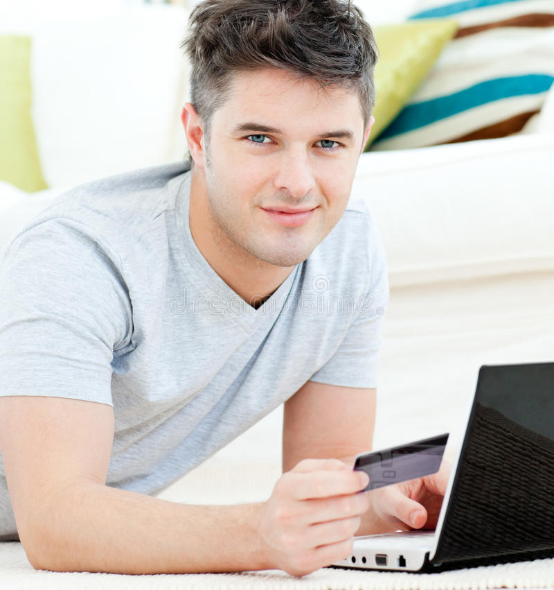 Download Charming Young Man With Card And Laptop Lying Stock Photo - Image: 15518116