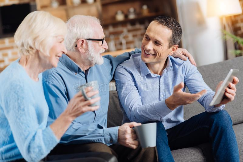 Charming young man having discussion with his senior parents. Pleasant discussion. Handsome young men sitting on the sofa next to his senior parents, holding a royalty free stock images