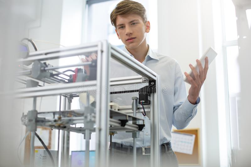 Charming young man learning structure of extruder. New knowledge. Pleasant young man learning the structure of extruder of a 3D printer while holding a tablet stock photo
