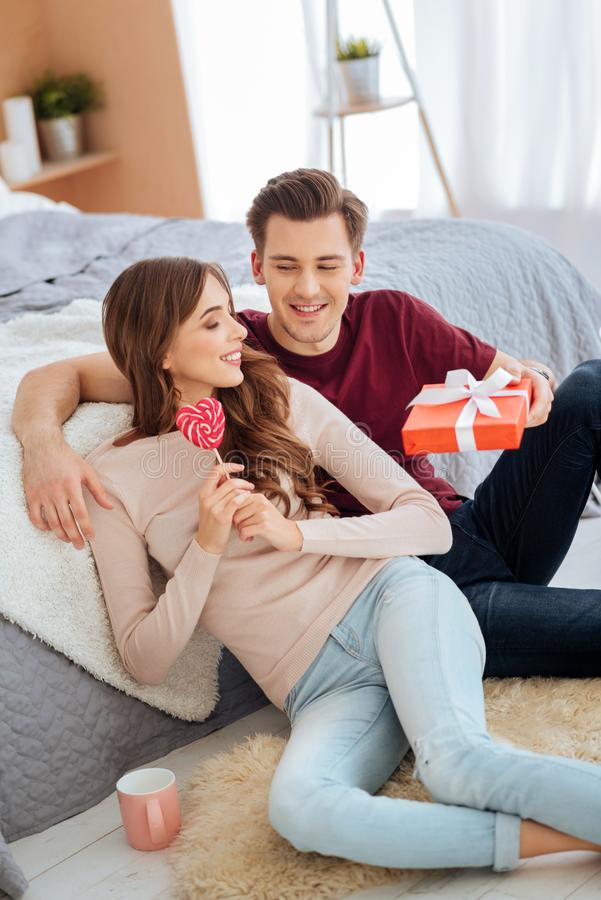 Charming young people enjoying romantic conversation at home. Love is in the air. Top view on a relaxed couple grinning broadly while congratulating each other royalty free stock images