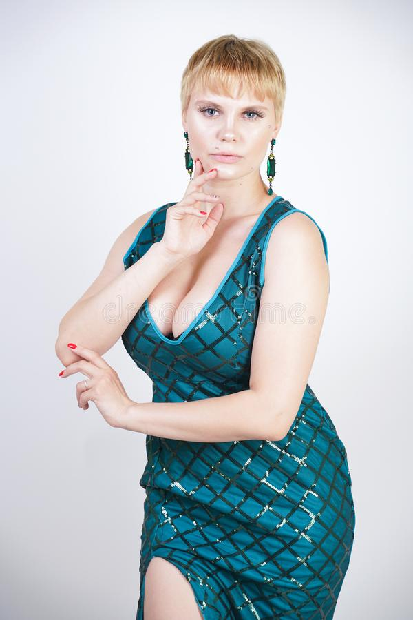 Charming young plus size woman with short blonde hair dressed in a luxurious long evening green dress with sequins and stands on a stock photos