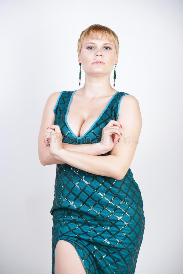 Charming young plus size woman with short blonde hair dressed in a luxurious long evening green dress with sequins and stands on a stock photography