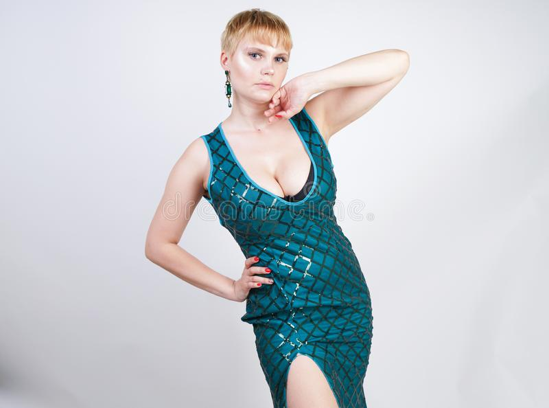 Charming young plus size woman with short blonde hair dressed in a luxurious long evening green dress with sequins and stands on a royalty free stock images