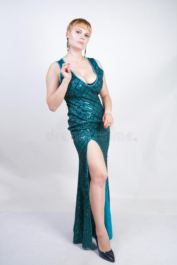 Charming young plus size woman with short blonde hair dressed in a luxurious long evening green dress with sequins and stands on a royalty free stock image