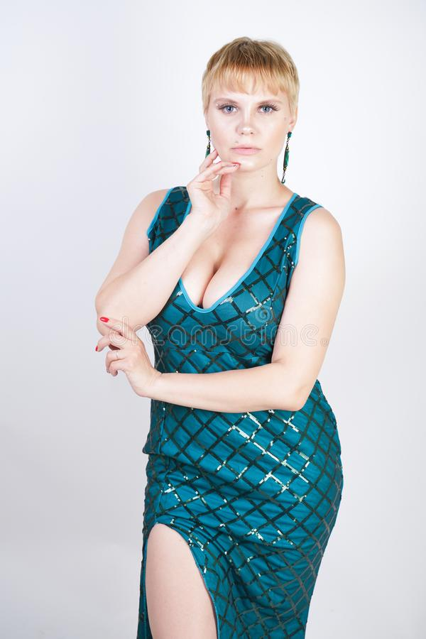 Charming young plus size woman with short blonde hair dressed in a luxurious long evening green dress with sequins and stands on a stock image