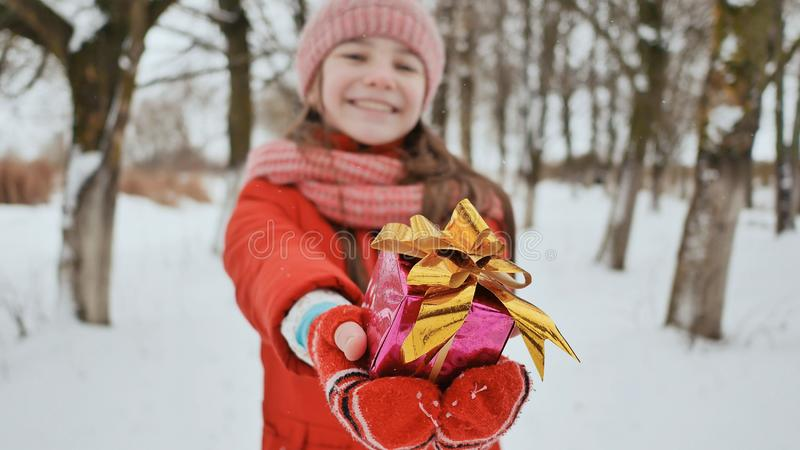 The charming young schoolgirl joyfully holds in her hands a packaged box with a gift in the winter forest. In. Anticipation of the New Year holidays stock photo