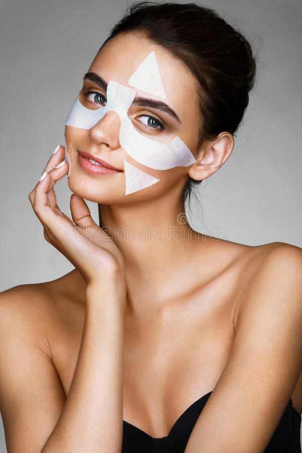Charming young woman with cotton facial mask. royalty free stock photos