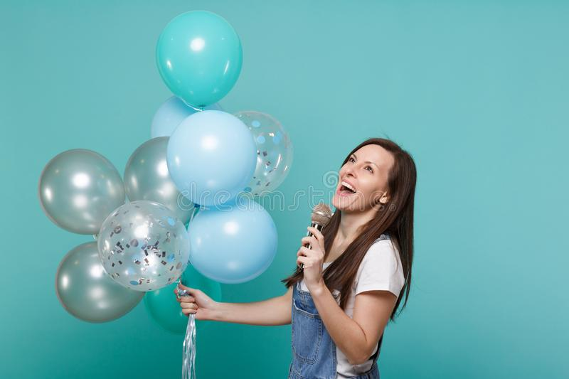 Charming young woman in denim clothes looking up sing song in microphone, celebrating hold colorful air balloons. Isolated on blue turquoise background royalty free stock image