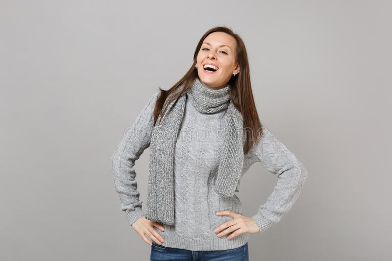 Charming young woman in gray sweater, scarf standing with arms akimbo on grey background in studio. Healthy royalty free stock photos