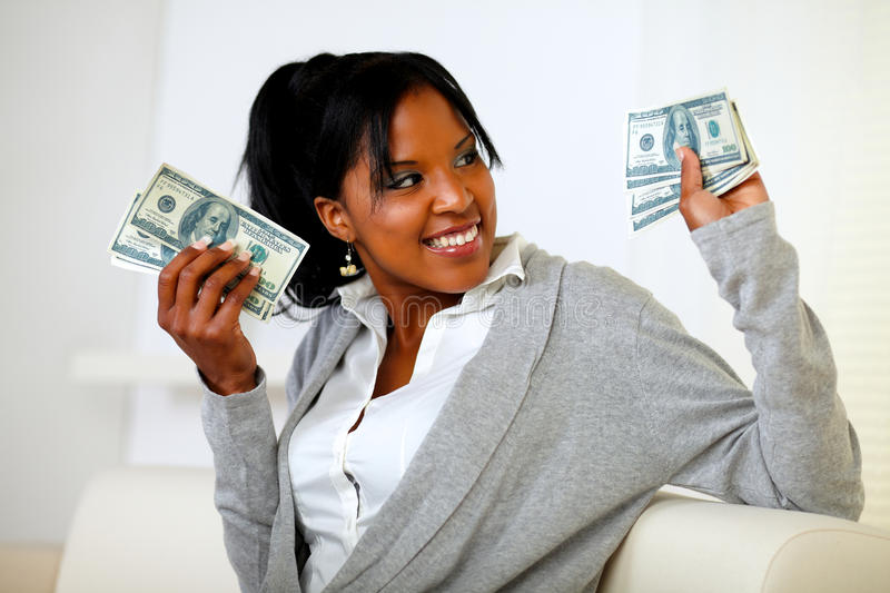 Charming young woman holding plenty of cash money royalty free stock photography