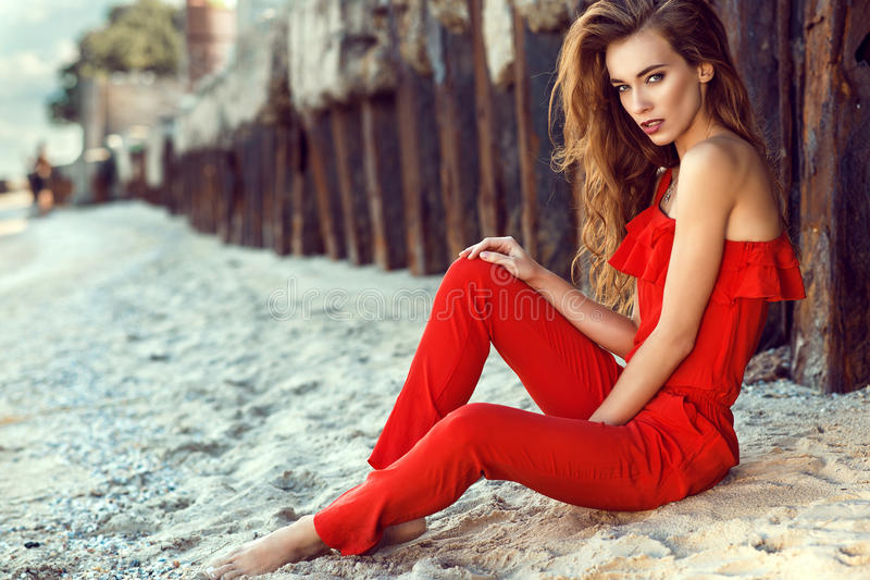 Charming young woman with long hair in coral red one shoulder jumpsuit sitting on the beach at the old rusty piles royalty free stock photo