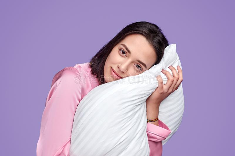 Charming young woman in pajamas with pillow. Pretty young female in pink nightwear hugging pillow while standing on purple background and looking at camera royalty free stock images