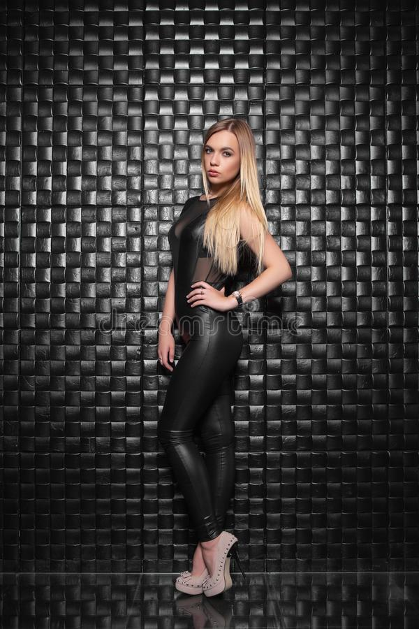 Charming young woman. Posing in the studio, dressed in a black leather suit royalty free stock photography