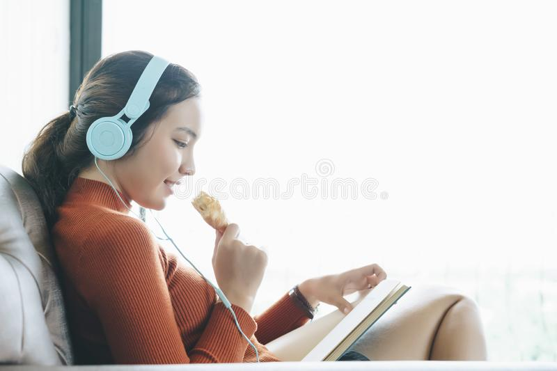 Charming young woman sitting on sofa eating a croissant and reading a book. stock photography